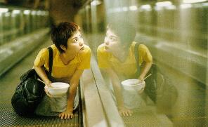 A scene from the movie Chungking Express: a woman on an escalator, beside her own reflection